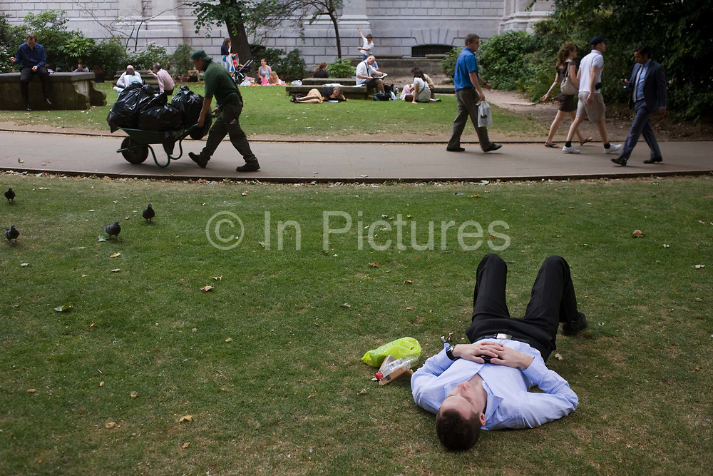 During a weekday lunchtime in the City of London, a young man sleeps on the grass in St. Paul's Churchyard, near the outer walls of the cathedral. Office workers have gathered with friends and colleagues taking advantage of warm weather to lie on the grass and eat their lunches. The man is asleep on the short lawn, having spent 20 minutes fiddling with his iPhone, scrolling through messages and sending emails after finishing his own sandwich, which has been put away next to his prone body, in a plastic bag. A council worker pushes a wheelbarrow along the path laden with refuse as the young man lies resting before another afternoon at his nearby desk.