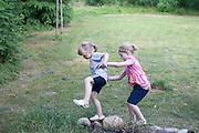 Young Polish girls balancing on fieldstone rocks in their yard. Zawady Central Poland
