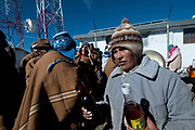 Bolivia,  June 2013. La Cumbre , near La Paz, 15,260 feet, 4,650 metres . 21st June Aymara New Year (Machaq Mara) , the winter solstice when the sun  comes to earth and signifies the time for planting and new growth. A man serves alcohol to his friends.