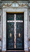 """""""Central bronze doors of Saint Paul Outside the Walls with inlaid silver Cross and Stations of Saints Peter and Paul""""…<br /> <br /> There are three main doors. At the center, is the monumental door in green bronze made by Antonio Maraini, which was placed here in 1931; to its right is the new Holy Door, made of golden bronze, created by the sculptor Enrico Manfrini and erected for the Jubilee of the year 2000. The central door shows episodes relating to the lives and preaching's of Saints Peter and Paul. A large cross with inlaid silver and embellished with stones of lapis lazuli overlays the door from side to side. The cross on the drawing represents a cross motif in curlicued silver, and this has on its plaques in lapis lazuli. Four on the horizontal bar show the symbols of the Evangelists, and on the vertical bar are the symbols of the Apostles. The reliefs (left to right) on the door show scenes from the lives, apostolates, and martyrdoms of Saints Peter and Paul, according to the wishes of the abbot of the monastery. Apart from the two central scenes, all of the events depicted took place in Rome. The reliefs depict: <br /> 1)Coat of arms of the Church <br /> 2)Coat of arms of Rome <br /> 3)The Crucifixion of St Peter <br /> 4)""""Domine, Quo Vadis?"""" <br /> 5)Christ Giving the Keys to St Peter <br /> 6)Foundation of the Papal See <br /> 7)St Peter Baptizing in the Catacombs <br /> 8)The Beheading of St Paul <br /> 9)The Conversion of the Centurion <br /> 10)St Paul's Conversion <br /> 11)St Paul Teaching in Rome <br /> 12)St Paul Reaches Rome and is Welcomed by the Faithful"""