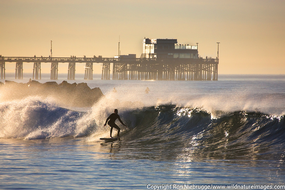 Surfing Newport Beach with the Newport Pier in the background, Orange County, California.