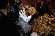 A girl and her family in Oruro, Bolivia, buy bread with which to decorate the shrine that they will build at Todos Santo for her dead father who died two years before. In the Altiplano of Bolivia, it is customary that a family, in which there has been a death within the last three years, build a shrine at home at Todos Santos, decorating it with religious symbols as well as a picture of the deceased and food and drink that he or she liked, and then call down the spirit for a three day visit. The bread is a particularly important type of decoration. There are pieces of bread shaped like human beings, representing the dead, and there are also pieces in the shape of various old Inca symbols such as the sun and the moon.