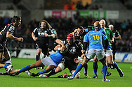 Alun Wyn Jones of the Ospreys © is brought down by Alberto Sgarbi.  Heineken cup, season 2012-2013, pool 2 match, Ospreys v Benetton Treviso at the Liberty Stadium in Swansea, South Wales on Friday 12th October 2012.  pic by  Andrew Orchard, Andrew Orchard sports photography,