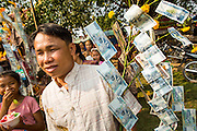 16 MARCH 2013 - NONG SA, LAOS: A man carries a tree of money to make merit at the temple fair at Wat Nong Sa in the village of Nong Sa, which is on Highway 13, in Vientiane province of Laos.PHOTO BY JACK KURTZ