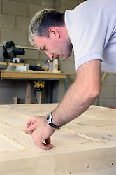Man with learning disability doing woodwork; assembling wooden wardrobe,