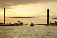 A tug boat passes under the Talmadge Memorial Bridge in Savannah, Georgia at sunset..