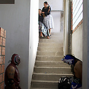 Cholita wrestlers Martha La Altena and Claudina the Condemned (top) prepare their hair as their male counterparts wait pensively for their bout during the 'Titans of the Ring' wrestling group performance each at El Alto's Multifunctional Centre. Bolivia. The wrestling group includes the fighting Cholitas, a group of Indigenous Female Lucha Libra wrestlers who fight the men as well as each other for just a few dollars appearance money. El Alto, Bolivia, 14th march 2010. Photo Tim Clayton