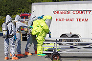 New Hampton, New York - A member of the Orange County Hazardous Materials (HAZMAT) Response Team, gets ready to remove his protective suit after going through a decontamination wash during a drill that practiced responding to a tanker railcar leak at the Orange County Fire Training Center on Aug. 9, 2014. The Huguenot Fire Department provided the decontamination team.