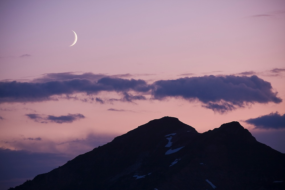 A crescent moon rises over clouds and mountains at twilight in Glacier Peak Wilderness, Washington.