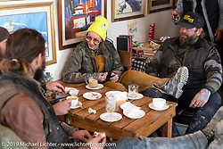 Danita Gayle having coffee with tattoo artist Justin Big Meas Wilson in Kalipani's Himalayan Java Coffee shop during Motorcycle Sherpa's Ride to the Heavens motorcycle adventure in the Himalayas of Nepal. On the fifth day of riding, we went from Muktinath to Tatopani. Friday, November 8, 2019. Photography ©2019 Michael Lichter.