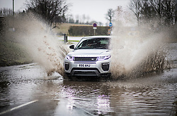 © Licensed to London News Pictures. 30/01/2021. Redbourn, UK. A car ploughs through deep surface water in the town of Redbourn, Hertfordshire, caused by heavy rain and snowfall. Parts of the UK continue to suffer from flooding caused by Storm Christoph. Photo credit: Ben Cawthra/LNP