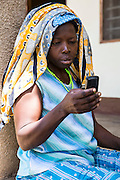 Salima Ally, a 64 year old grandmother who is staying at the hospital with her sick grandchild checks her mobile phone for a text message with information about her next appointment. VSO has help set up an SMS platform for the hospital to make it easier for patients to attend their appointments with the Doctor. St Walburg's Hospital, Nyangao. Lindi Region, Tanzania.