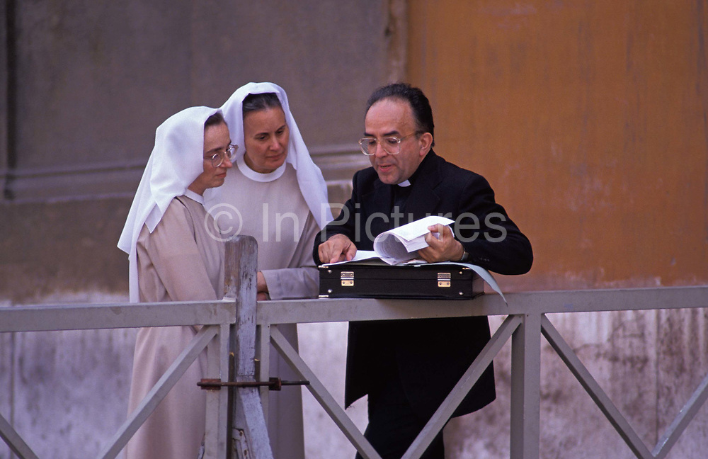 A Catholic priest leans his briefcase on railings to show a document to two nuns in St. Peters Square, on 3rd November 1999, in Vatican City, Rome, Italy.