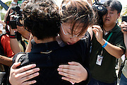 14 SEPTEMBER 2003 - CANCUN, QUINTANA ROO, MEXICO:  The daughters of Lee Kyung-hae comfort each other at an alter for their father during a memorial service Sunday for her father, a Korean farm activist who publicly committed suicide Wednesday in Cancun to protest World Trade Organization agricultural policies, has been built where he died in a park in Cancun. Thousands of protestors opposed to the World Trade Organization and globalization have come to Cancun to protest the WTO meetings taking place in the hotel zone. Mexican police restricted most of the anti-globalization protestors to downtown Cancun, about five miles from the convention center.  PHOTO BY JACK KURTZ