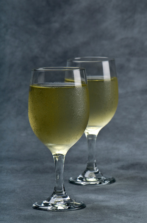 Cup of chilled white wine in gray background. Space for copy.