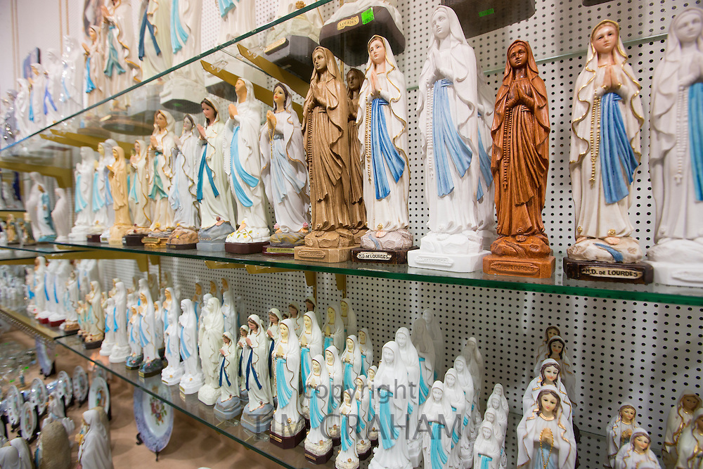 Religious statues on sale in gift shop in the pilgrimage town of Lourdes in the Pyrenees, France