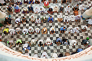 """Sept. 25, 2009 -- PATTANI, THAILAND: Men gather for Friday prayers in the Central Mosque in Pattani, Thailand. The mosque's Imam said a special prayer on this day for the Thai King who is in a hospital in Bangkok. Pattani's Central Mosque is considered the most architecturally striking mosque in Thailand and was a leading tourist site until the current violence put an end to mass tourism in Pattani. Thailand's three southern most provinces; Yala, Pattani and Narathiwat are often called """"restive"""" and a decades long Muslim insurgency has gained traction recently. Nearly 4,000 people have been killed since 2004. The three southern provinces are under emergency control and there are more than 60,000 Thai military, police and paramilitary militia forces trying to keep the peace battling insurgents who favor car bombs and assassination.  Photo by Jack Kurtz"""