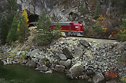 Idaho, Smiths Ferry. Scenic Railroad. Train engine of the Thunder Mountain Line passes through tunnel along Payette River.