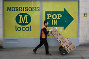 A delivery man pushes a trolley loaded with boxes past a sign for the supermarket chain, Morrisons, on 25th January 2018, in London, England.