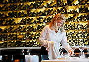 SHOT 12/11/10 4:58:51 PM - A server polishes silverware in the dining room prior to that evening's dinner service at Frasca Food and Wine in Boulder, Co. Frasca is a highly-rated neighborhood restaurant inspired by the cuisine and culture of Friuli, Italy. Historically found throughout Friuli, Frascas were friendly and informal gathering places, a destination for farmers, friends, and families to share a meal and a bottle of wine. Identified by a tree branch hanging over a doorway portal, they were a symbol of local farm cuisine, wine, and warm hospitality. (Photo by Marc Piscotty / © 2010)