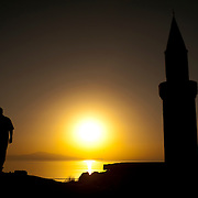 The setting sun casts vivid colors across Van Lake, and silhouettes a man and the minaret of the mosque at Van Castle (Kalesi), Van Province, Eastern Anatolia, Turkey.