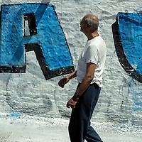South America, Argentina, Buenos Aires. Man walks along stret reading wall of graffiti.