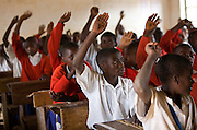 School children put up their hands to answer questions in Ikuna village primary school during class run by a Student Partnerships Worldwide (SPW) volunteer.