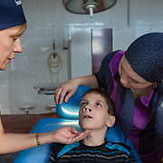 CAPTION: Dr Fomenko examines Kirill Fedorenko, prior to his hard palate operation, and explains what she'll need to do to Tatiana, his step-mother. LOCATION: Volgograd City Hospital #1, Volgograd, Russia. INDIVIDUAL(S) PHOTOGRAPHED: From left to right: Dr Irena Fomenko, Kirill Fedorenko and Tatiana Fedorenko.