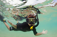 A young child snorkeling off the coast of Hawaii.