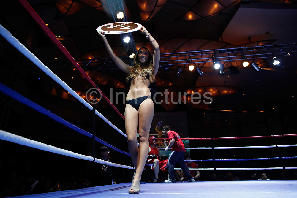 Ring girls display placards during a bout at the Brawl on the Bund event on Saturday, 11 December 2010. The event features 7 pairs of amateur boxers selected from Shanghai's expatriate community.