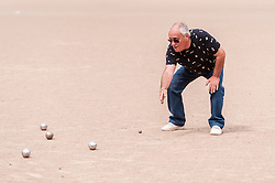 """© Licensed to London News Pictures. 05/06/2015.   London, UK. A French coach gives advice, as media and guests take part in """"Freddie for the Day"""", some dressing up as Queen's lead singer, Freddie Mercury, by playing a special game of celebrity Pétanque, competing for the Londonaise 'Celebrity Pétanque Trophy', ahead of The Londonaise Pétanque festival this weekend in Barnard Park, Islington.  The festival will set a new precedent in the UK with 128 teams taking part in the main tournament.  The event also aims to raise funds for the Mercury Phoenix Trust to fight against AIDS worldwide. Photo credit : Stephen Chung/LNP"""