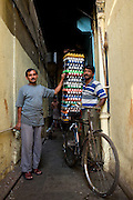 An egg delivery man (r), his boss (l) and a factory worker (background) in a back alley on Modi Street near Gulshan Haircutting Salon.  Again, a classic double top tube Hercules utility bike is the steed of choice for overburdened jobs like this- Bombay/Mumbai - India