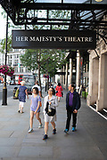 People pass outside Her Majestys Theatre in London, United Kingdom. Her Majestys Theatre is a West End theatre situated on Haymarket.