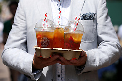 A spectator carries a drinks holder containing Pimms on day four of the Wimbledon Championships at the All England Lawn Tennis and Croquet Club, Wimbledon.