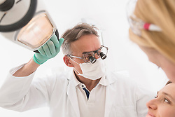 Close-up of dentist examining patient with magnifiers on eyeglasses, Munich, Bavaria, Germany