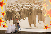 Moscow, Russia, 05/11/2005..A bride and groom on Red Square in front of decorations erected for a military parade on November 7 to commenorate a similar parade during World War Two when soldiers left for the front.