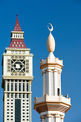 Detail of contrast between mosque minaret and modern skyscraper in Dubai United Arab Emirate