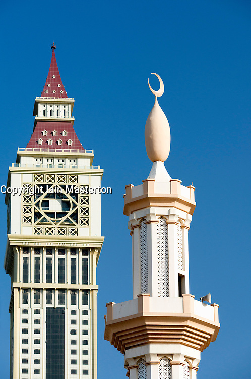 Detail of contrast between mosque minaret and modern skyscraper in Dubai United Arab Emirate