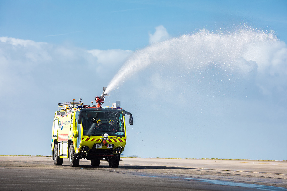 Firemen driving a fire engine on the runway at Jersey Airport and squirting water out of the fire hose.