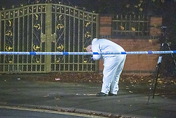© Licensed to London News Pictures. 11/11/2020. Slough, UK. A forensic investigator takes a photograph of evidence on Bradley Road. A person was reportedly stabbed in Slough on Tuesday 10/11/2020. A large cordon was put in place by Thames Valley Police centred around shops on Stoke Poges Lane and included a large section of Bradley Road. Photo credit: Peter Manning/LNP