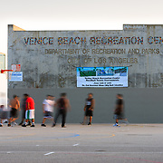 A group of guys plays basketball on Muscle Beach in Los Angeles California at sunset.