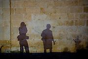Night-time shadows of tourist photographer and elderly local woman, wall of Church of Saint Mark, Makarska, Croatia