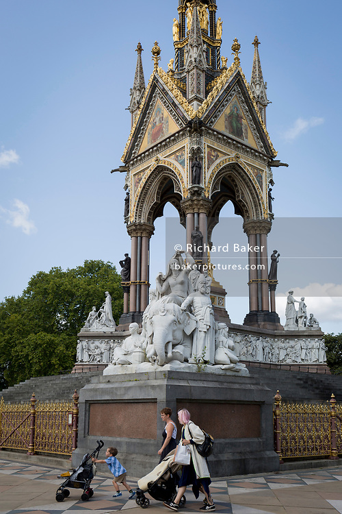 Mothers and children walk in front of the golden ironwork at the Albert Memorial in Kensington Park, on 20th August 2019, in London, England. The Albert Memorial, directly north of the Royal Albert Hall in Kensington Gardens, London, was commissioned by Queen Victoria in memory of her beloved husband Prince Albert, who died in 1861. Designed by Sir George Gilbert Scott in the Gothic Revival style, it takes the form of an ornate canopy or pavilion 176 feet tall, in the style of a Gothic ciborium over the high altar of a church, sheltering a statue of the prince facing south. It took over ten years to complete, the £120,000 cost met by public subscription.