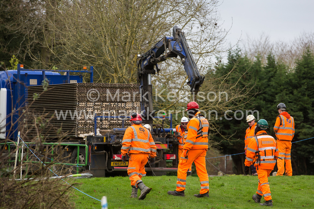 Denham, UK. 4 February, 2020. Engineers and security guards walk across land cleared for works for the HS2 high-speed rail link project. Behind other engineers prepare to unload a temporary roadway from a large truck. Planned works in the immediate vicinity are believed to include the felling of 200 trees and the construction of a roadway, Bailey bridge, compounds, fencing and a parking area.
