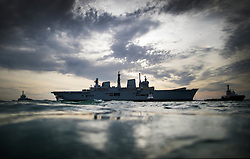 © Licensed to London News Pictures. 07/12/2016. Portsmouth, UK. Tugs tow the former Royal Navy aircraft carrier HMS Illustrious from Portsmouth throught The Solent  on her final voyage to a scrap yard. Illustrious, the last of the Invincible Class carriers, has been sold to the Leyal Ship Recycling and Dismantling company in Aliaga, Turkey - the same yard dismantled her sister ships Ark Royal and Invincible. Photo credit: Peter Macdiarmid/LNP