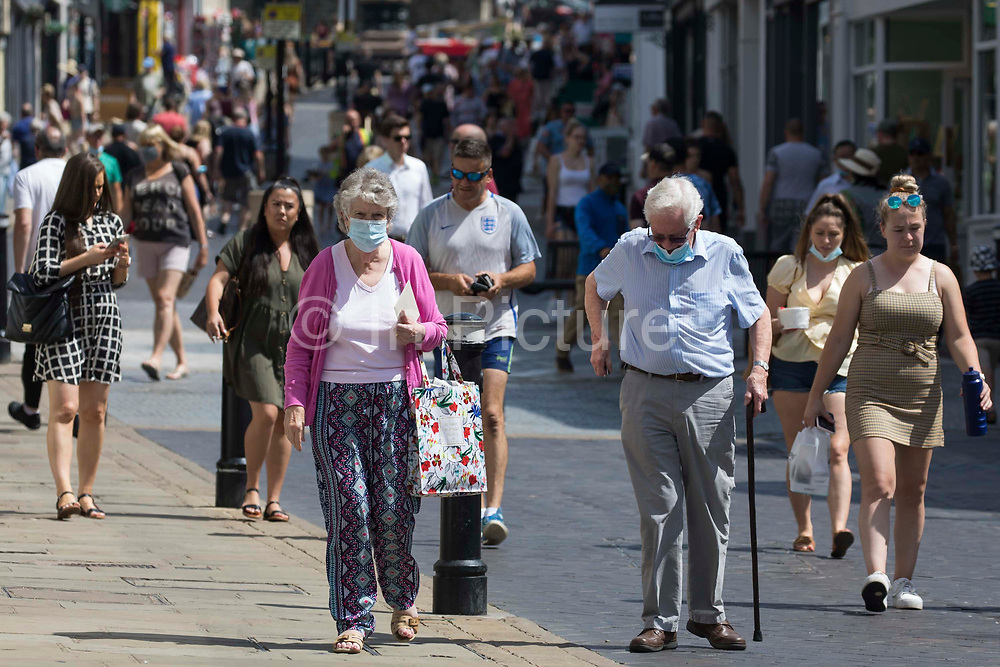 Shoppers and visitors, some of whom wearing face coverings, are pictured on Freedom Day, when the UK government lifted almost all remaining Covid-19 restrictions in England, on 19th July 2021 in Windsor, United Kingdom. Social distancing restrictions have been removed and face coverings are no longer required by law, although their use is recommended in crowded and enclosed spaces. Cases of the coronavirus are now expected to surge across the UK, which currently has the highest rate of daily recorded Covid-19 cases in the world.