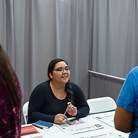 Christina Tsosie of the Gallup Independent greets students as they pas by her booth in the Wellness Center at the NTU campus for the Career Fair in Crownpoint on Thursday.