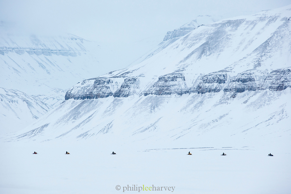A tour of snowmobiles travel towards the Von Post Glacier in Spitsbergen. Spitsbergen is the largest island of the arctic archipelago Svalbard, of Norway