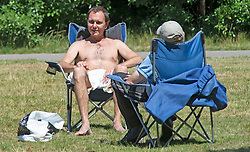 ©Licensed to London News Pictures 22/06/2020<br /> Greenwich, UK. A man sitting in a camping chair sunbathing with his top off. A warm sunny day in Greenwich park, Greenwich, London. The UK to enjoy hot heatwave weather this week with temperatures set to bring the hottest day of the year so far. Photo credit: Grant Falvey/LNP