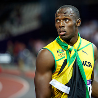 Usain Bolt stares towards the track infield as the Jamaican 4x100m relay team is interviewed by the media after winning gold and setting a new world record of 36.84 seconds during the 2012 London Summer Olympics.